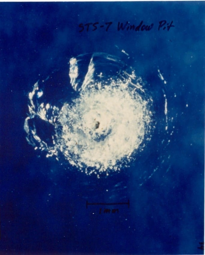 An impact crater on one of the windows of the Space Shuttle Challenger following a collision with a micrometeoroid during STS-7.